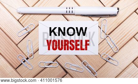 On A Background Of Wooden Blocks, A White Pen, White Paper Clips And A White Card With The Text Kow