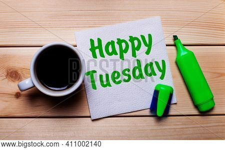 On A Wooden Table, A Cup Of Coffee, A Green Marker And A Napkin With The Text Happy Tuesday