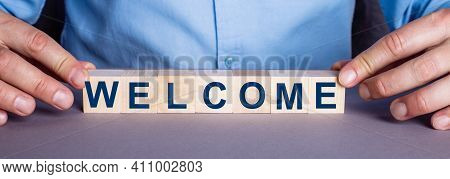 The Word Welcome Is Made Up Of Wooden Cubes By A Man. Business Concept