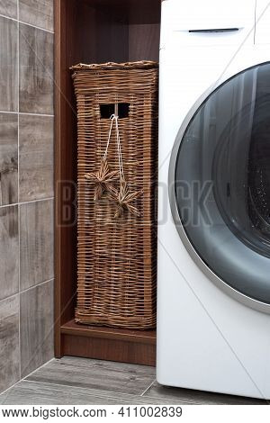 Wicker Laundry Basket Stands In A Wooden Closet Near A Modern Washing Machine In A Laundry Room. Sca
