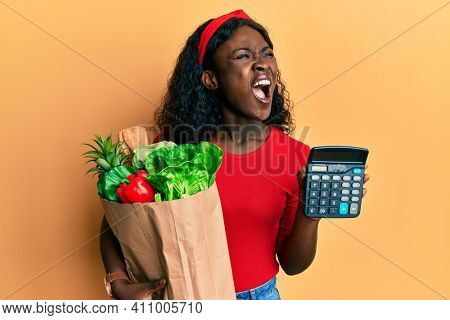 Beautiful african young woman holding groceries and calculator angry and mad screaming frustrated and furious, shouting with anger. rage and aggressive concept.