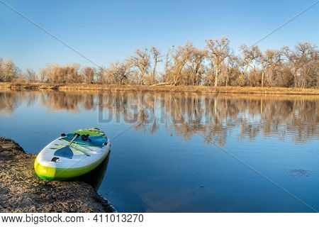 inflatable stand up paddleboard on a lake in early spring - Prospect Ponds, one of nature areas along the Poudre River in Fort Collins, Colorado