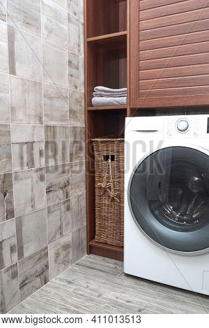 Scandinavian Interiors Of Laundry Room. Wicker Laundry Basket And Clean Cotton Towels In A Wooden Cl