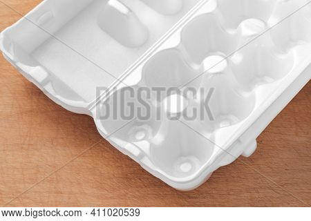 White Egg Packaging Lies On A Wooden Table.