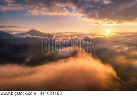 Mountains In Clouds At Sunrise In Summer. Aerial View Of Mountain Peak In Fog. Beautiful Landscape W