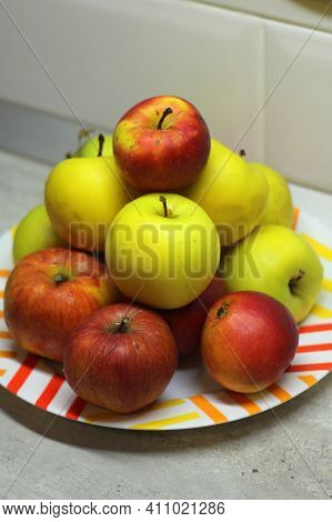 A Heap Of Apples In A Plate On The Table. Red And Green Juicy Ripe Apples Lie In A Slide On A White