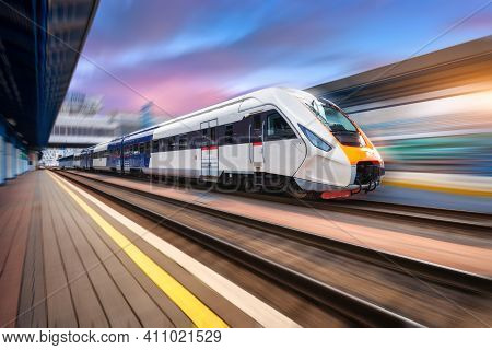 High Speed Train In Motion On The Railway Station At Sunset. Fast Moving Modern Passenger Train On R