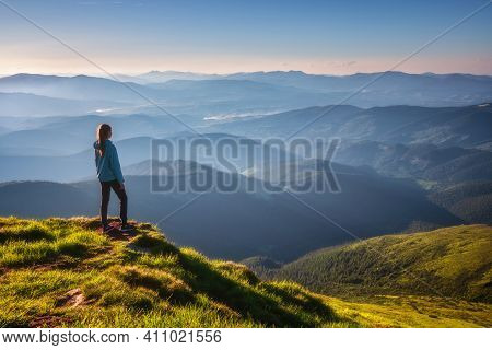 Girl On Mountain Peak With Green Grass Looking At Beautiful Mountain Valley In Fog At Sunset In Summ