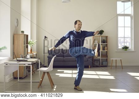 Mature Freelance Worker Exercising Taking Break During Working Day At Office