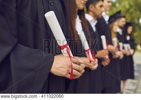 University Graduates Hands Holding Diplomas After University Graduating