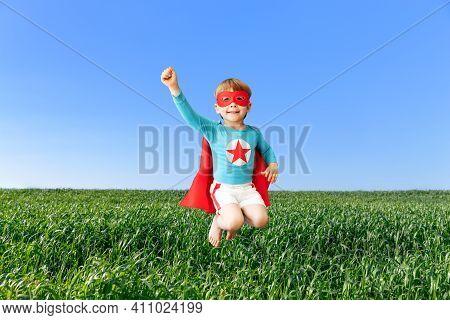 Happy Superhero Child Jumping Against Blue Sky. Super Hero Kid Having Fun In Spring Green Field Outd