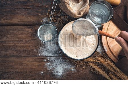 The Cook Mixes The Leaven Against The Background Of Wheat Flour And Water. The Concept Of Making Bre