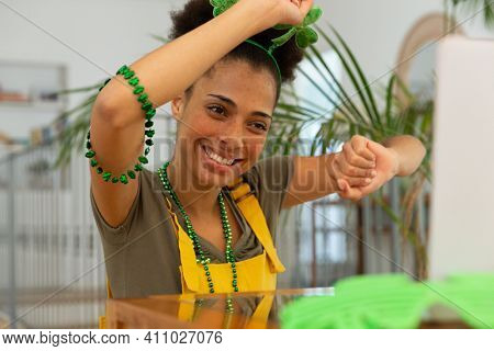 Happy mixed race woman celebrating st patrick's day making video call and dancing. in her seat. staying at home in isolation during quarantine lockdown.