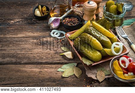 Delicious, Crunchy Pickles On A Wooden Background With , Onions, Garlic And Bay Leaf.