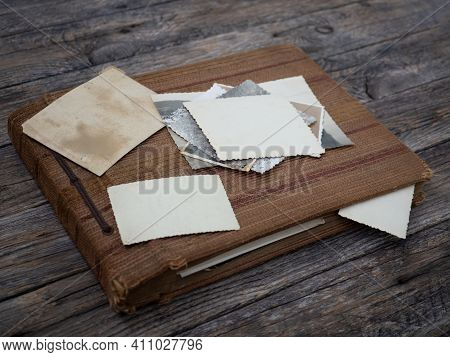 Old Shabby Family Photo Album With Photo On An Old Wooden Table. Family Traditions, Memory And Nosta