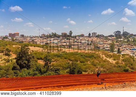 A Red Dirt Road Into The Slums Of Kibera In Nairobi, Kenya.