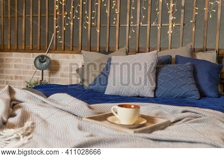 Coffee Cup Or Hot Tea In The Morning On The Bed Background.bedroom View. Grey And Blue Linen Pillows