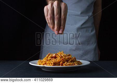 Italian Pasta On A Dark Background. Hand Sprinkles Salt On The Pasta. The Chef Salt Food On A Black