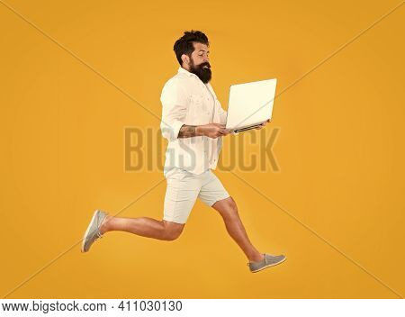 Portability Concept. Remote Job. Man Inspired Hold Laptop Jump. Run With Laptop. Hipster Bearded Man