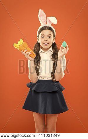 Adorable Happy Child Hold Eggs. Spring Holiday. Little Schoolgirl In Rabbit Ears Hold Carrot. Easter