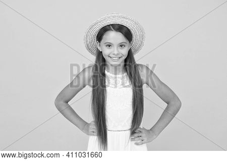 Hello. Cheerful Little Girl Wear Straw Hat. Beach Fashion For Kids. Small Child On Yellow Background