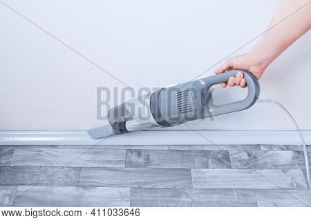 Handheld Gray Vacuum Cleaner In The Hand Of A Caucasian Woman. Vacuuming The Skirting Board.