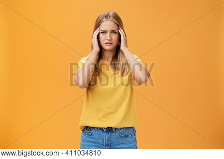 Portrait Of Drained Sad Young Woman With Tanned Skin And Fair Hair Feeling Discomfort In Head Touchi