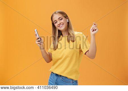 Joyful Carefree European Woman Wearing Wireless Earbuds Holding Smartphone Dancing With Raised Hands