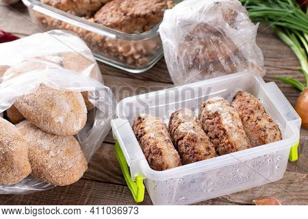 Frozen Cutlets Or Meatballs In Plastic Bag On A Wooden Table, Ready To Eat