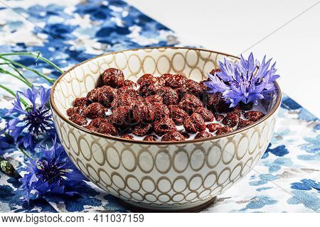 Breakfast Cereal, Chocolate Cereals In Milk With Cornflower Flower On A Natural Blue Napkin, Concept