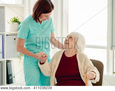 Old lady leaning on nurse hand to stand from chair in nursing home
