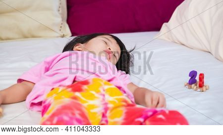 Little Asian Cute Girl Resting On Bed In Bedroom With Her Wooden Number Train Toy On Side. Child Fel