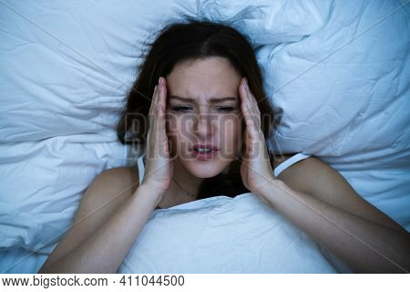 Stressed Woman With Headache Sleeping In Bed With Insomnia