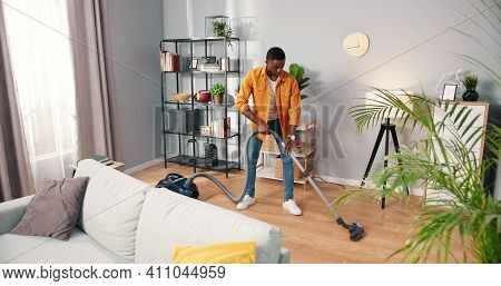 African American Busy Handsome Young Guy Vacuuming Cozy Living Room Doing Housework, Male Cleaning H