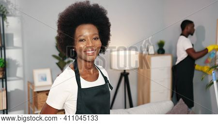 Close Up Of Happy Beautiful African American Young Woman In Black Apron Working Vacuuming Or Mopping