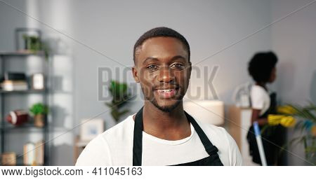 Close Up Portrait Of Joyful African American Handsome Young Male Worker In Apron Standing In Room Lo