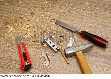 Shavings On Floor From Door Latch Installing. Wood Sawdust From Hole For Door Lock Making. Hammer, C