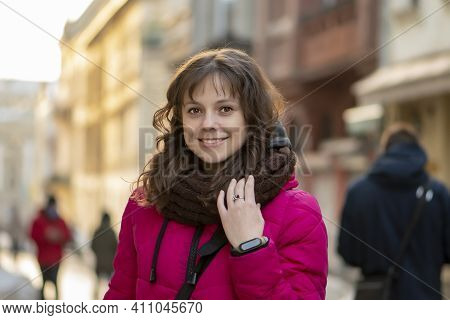 A Young Beautiful White Woman 30-35 Years Old With Curly Dark Hair Smiles Against The Backdrop Of A