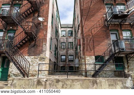 Lightwell Within An Old Apartment Building Flanked By Metal Fire Escapes, Horizontal Aspect