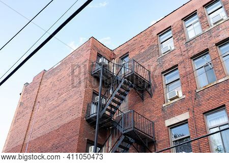 Oblique Upward View Of An Old, Generic Apartment Building With Metal Fire Escape, Horizontal Aspect