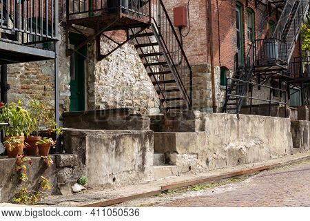 Rusted Metal Fire Escape Stairs And Crumbling Concrete Steps At The Back Side Of An Old Apartment Bu