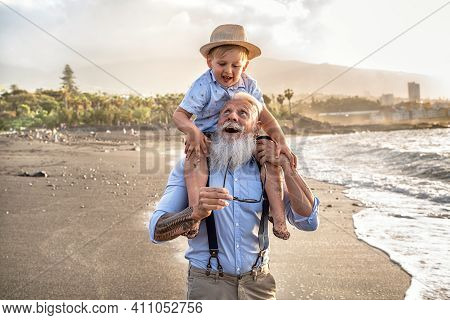 Happy Kid Playing On The Beach With His Grandfather, Celebrating Grandfather's Day Together, Smiling