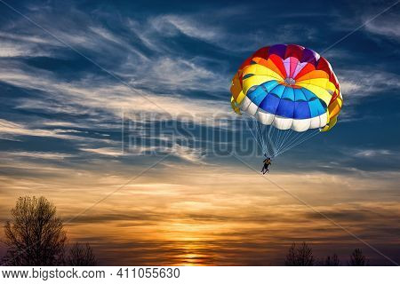 Gliding With A Parachute On The Background Of Bright Sunset.