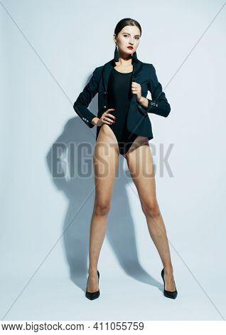 Fashion and people concept: beautiful fashion model woman with red lips wear black swimsuit and jacket over white background