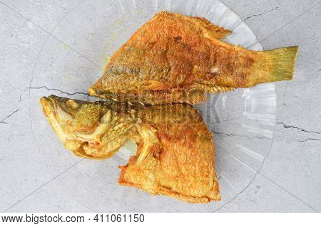 Top View Of Fried Barramundi Fish On A Glass Plate