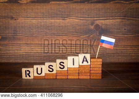 Russia. Politics, Development, Economics And Sanctions Concept. Wooden Alphabet Letters And Flag