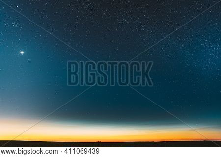 Night Starry Sky With Glowing Stars Above Countryside Field Landscape In Early Spring. Bright Glow O