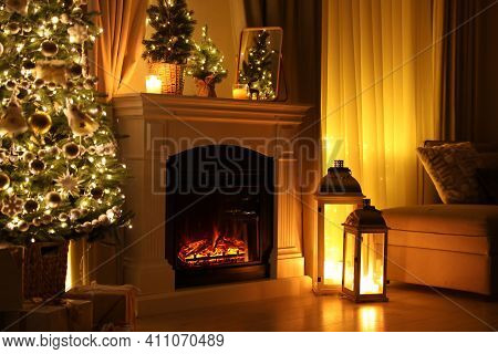 Beautiful Fireplace, Christmas Tree And Other Decorations In Living Room At Night. Interior Design
