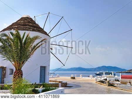 Famous White Windmill In Typical Greek Island Landscape On Summer Day. Cruise Liner Navigate Harbor.