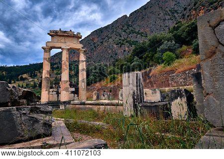 Ruins Of Tholos Of Ancient Greek Goddess Athena Pronaia In Delphi, Greece. Three Doric Columns By Fa